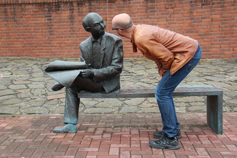 homme qui regarde la statue d'un homme